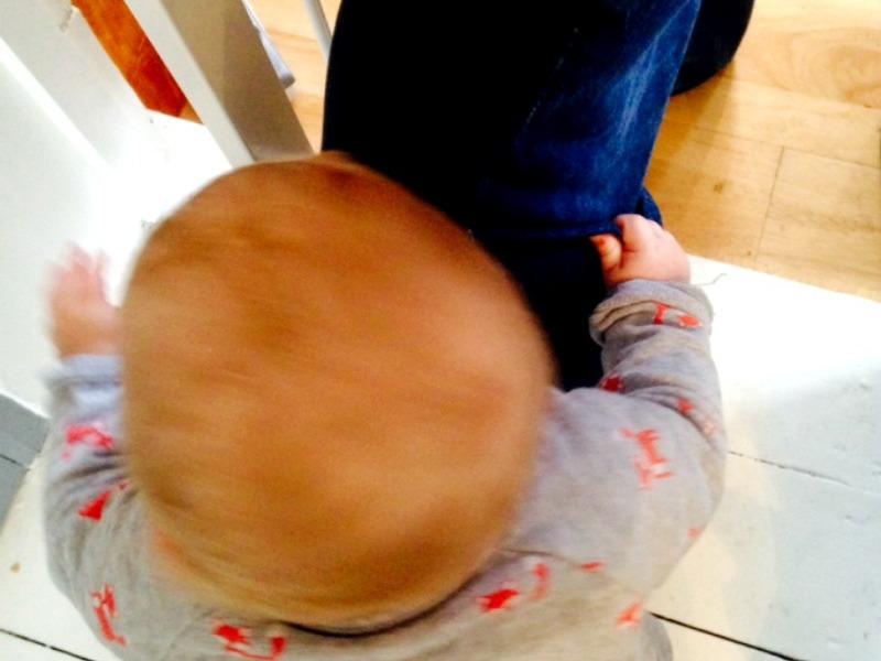 baby holding onto dad's leg